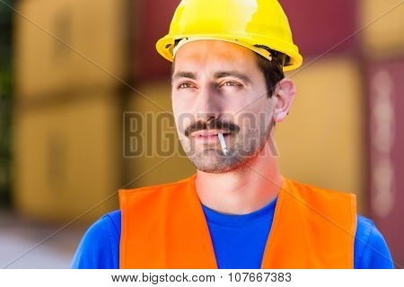 Smoking worker in logistics company with cigarette in front of containers