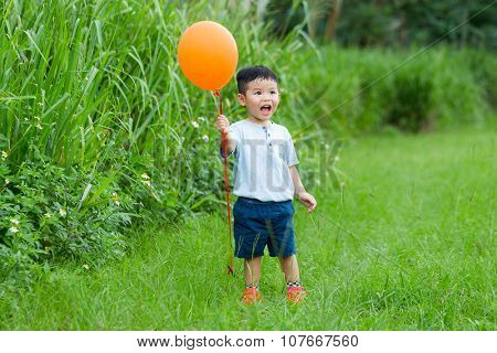 Thrilled little boy holding a flying ballon