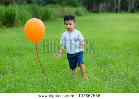 Little boy want to catch a flying ballon