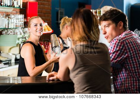 Young people or couple having a date in a club or bar, the bartender mixes a drink
