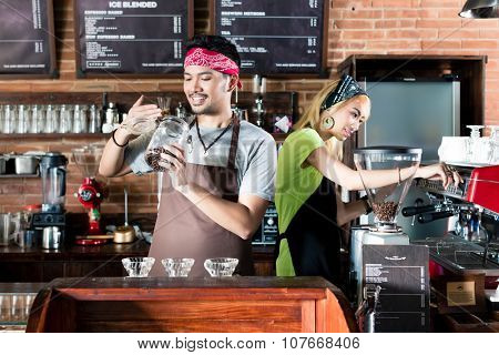 Woman and man in Asian cafe preparing coffee and smelling on fresh coffee beans