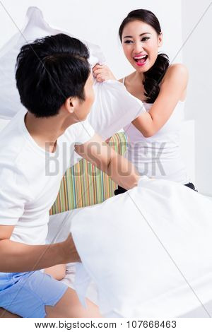 Chinese Woman and man having pillow fight