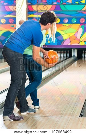 Young couple or friends, man and woman, playing bowling with a ball in front of the ten pin alley, he shows her how it works