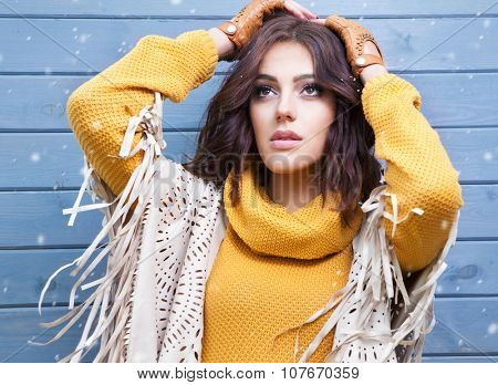 Beautiful natural young brunette woman, wearing tassel cape, covered with snow flakes. Snowing winter beauty concept.