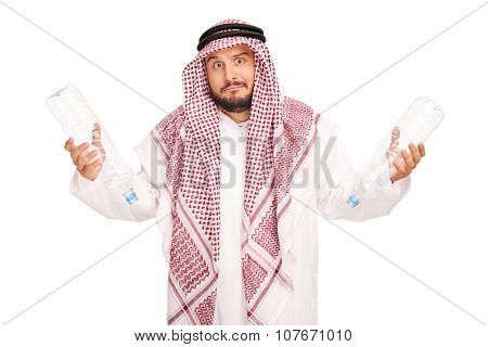 Sad young male Arab holding two empty plastic bottles and looking at the camera isolated on white background