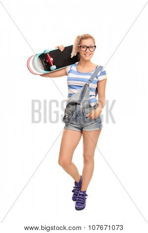 Full length portrait of a young blond hipster girl carrying a skateboard over her shoulder and looking at the camera isolated on white background