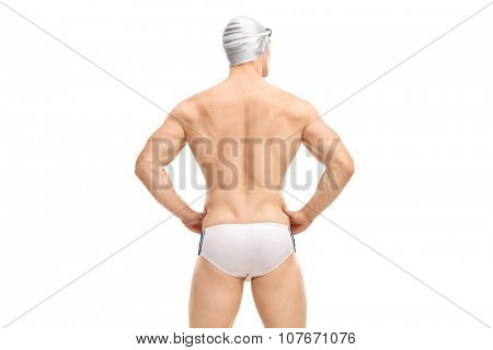 Rear view shot of a muscular male swimmer in white swim trunks and a gray swim cap isolated on white background