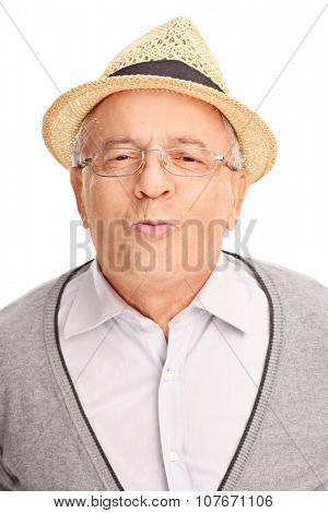 Vertical shot of a senior gentleman giving a kiss and looking at the camera isolated on white background