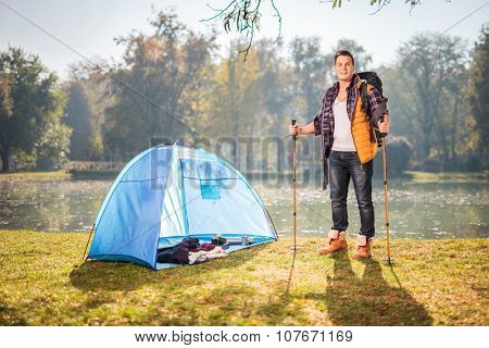 Young male hiker posing by a pond next to a blue tent in a field on a sunny autumn day
