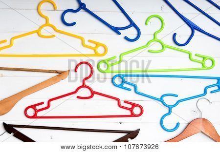 many different clothes hangers on white wooden background