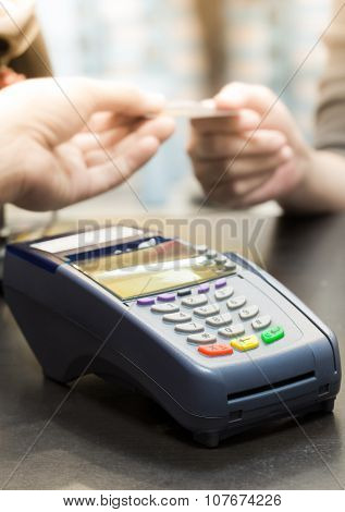 Credit Card Machine On The Table With Woman Handing Over Credit Card To Cashier In Background