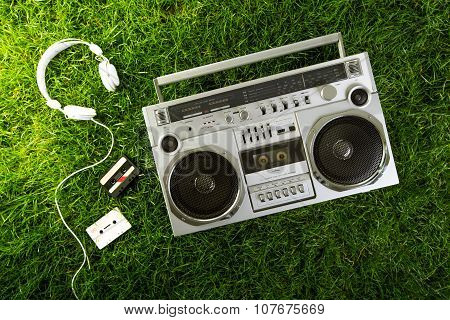 Retro-styled Silver Boom Box, Earphones And Audio Cassettes Over Green Grass Studio Shot