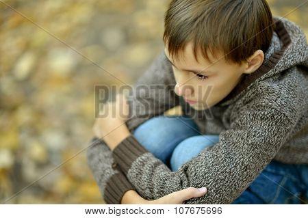 sad boy in autumn park