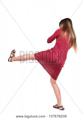 skinny woman funny fights waving his arms and legs. Isolated over white background. Long-haired girl in a red plaid dress hits right foot.