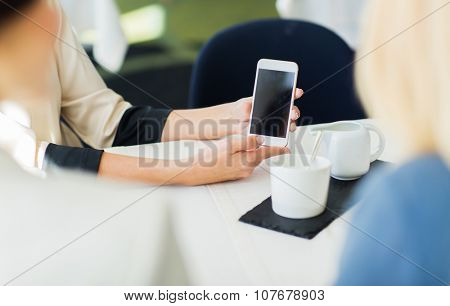 people, holidays, technology and lifestyle concept - close up of women with smartphone at restaurant