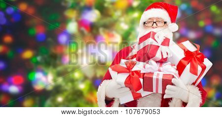 christmas, holidays and people concept - man in costume of santa claus with gift boxes over party lights background