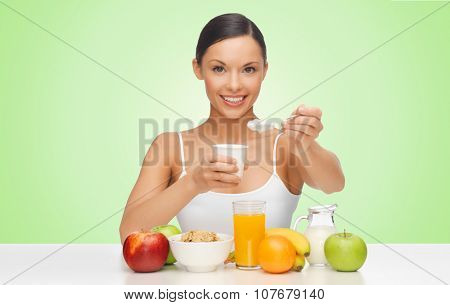 people, healthy food, diet and weight loss concept - happy beautiful woman with fruits eating yogurt for breakfast over green background