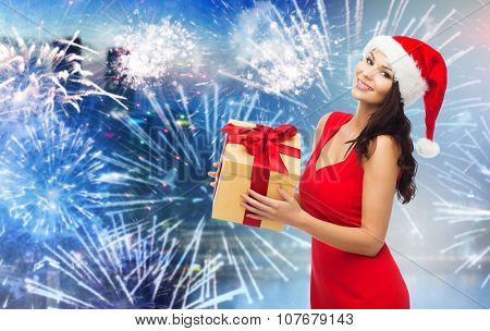 people, holidays, christmas, new year party and celebration concept - beautiful sexy woman in red dress and santa hat with gift box over night city and firework background