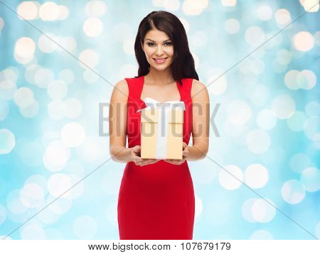 people, holidays, christmas, birthday and celebration concept - beautiful sexy woman in red dress with gift box over blue lights background
