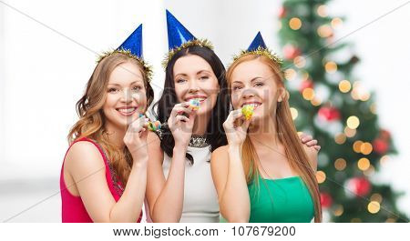 celebration, friends, bachelorette party, birthday concept - three smiling women wearing blue hats and blowing favor horns