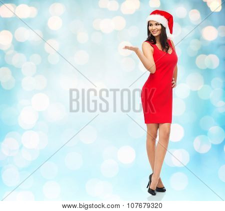 people, holidays, christmas and advertisement concept - beautiful sexy woman in santa hat and red dress showing something on empty hand over blue lights background