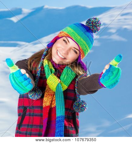 Portrait of cute smiling girl gesturing by hands good mood, wearing stylish colorful outfit, spending active winter holidays in the snowy mountains