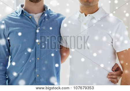 people, homosexuality, same-sex marriage, gay and love concept - close up of happy male gay couple hugging over snow effect