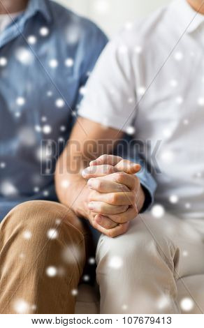 people, homosexuality, same-sex marriage, gay and love concept - close up of happy male gay couple holding hands over snow effect