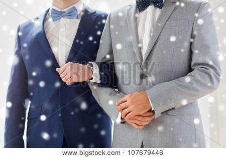 people, homosexuality, same-sex marriage and love concept - close up of happy male gay couple holding hands on wedding over snow effect