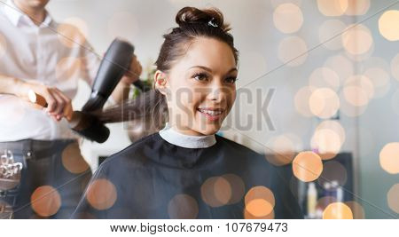 beauty, hairstyle and people concept - happy young woman and hairdresser with fan making hot styling at hair salon over holidays lights
