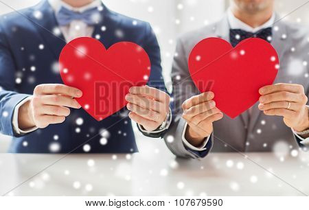 people, homosexuality, same-sex marriage, valentines day and love concept - close up of happy married male gay couple holding red paper heart shapes on wedding over snow effect