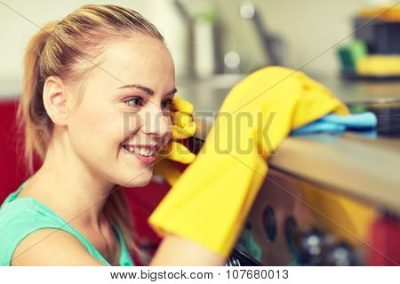 people, housework and housekeeping concept - happy woman cleaning cooker at home kitchen
