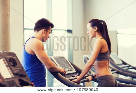 sport, fitness, lifestyle, technology and people concept - woman with trainer working out on treadmill in gym