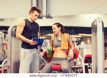 fitness, sport, exercising, technology and people concept - smiling young woman and personal trainer with tablet pc computer in gym