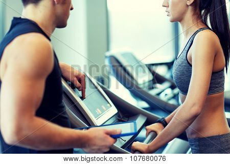 sport, fitness, lifestyle, technology and people concept - close up of woman with trainer working out on treadmill in gym