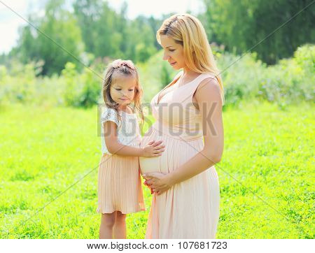 Happy Pregnant Woman, Little Child Daughter Touches Tummy Mother In Summer Day