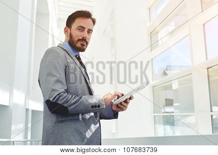 Handsome successful male office worker in suit using digital tablet during work break