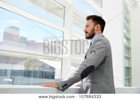 Confident businessman conceived looks in office window while rest after conference