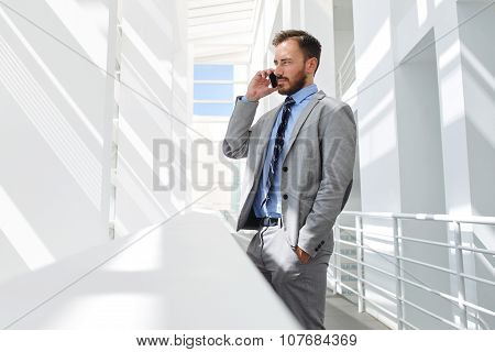 Male managing director having telephone conversation while resting after briefing