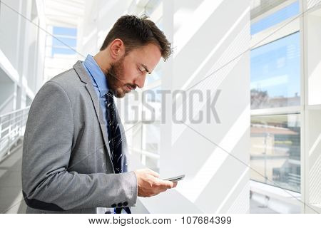 Young male financier chatting on cell telephone before business meeting with his partners