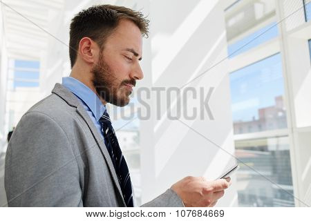 Young businessman concentrated looking at cell telephone while rest after conference