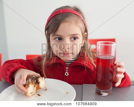 Little Girl Eating Donut With Juice