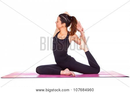 Beautiful woman doing Eka Pada Rajakapotasan pose on yoga class. Studio shot.