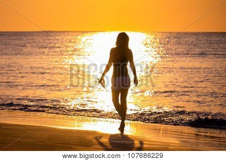 Woman on the beach in Bali Indonesia holding her sandals at sunset