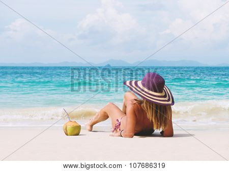 Happy young woman in straw hat with  on the beach with a coconut drink