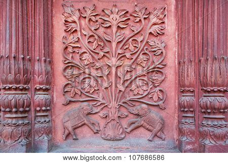 Two elephant under a tree of life. Bas-relief on the wall of an ancient temple in India.