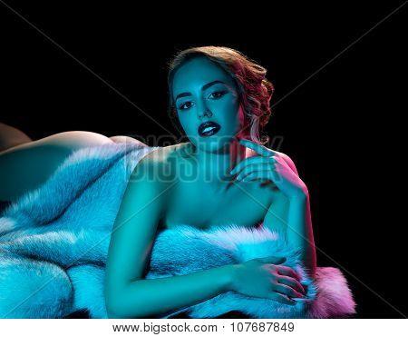 Elegant model posing nude with luxurious furcoat