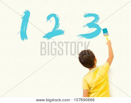 Llittle boy painting numbers 123 with brush on the wall