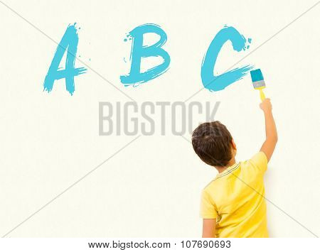 Little boy painting ABC with brush on the wall
