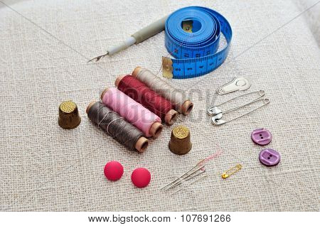 Items for sewing. Spools of sewing thread, pins, needles, buttons, flexible ruler to Tailor, thimble